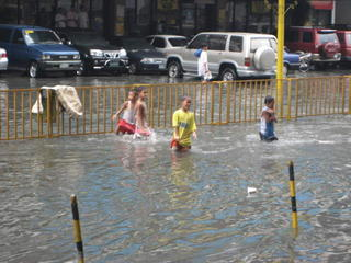 CHILDREN PLAYING IN THE RAIN, MANILA